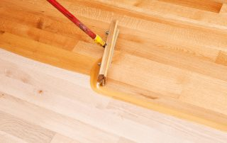 Squeegee Style Brush Applying Clear Polyurethane to Hardwood Floor